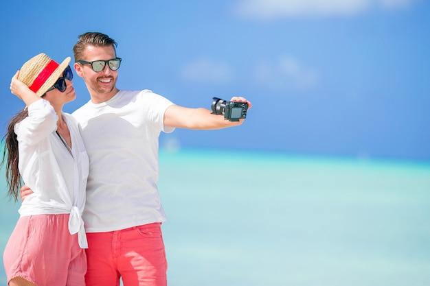 Pares felizes que tomam uma foto do selfie na praia branca. dois adultos curtindo suas férias na praia exótica tropical