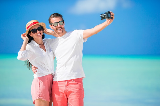 Pares felizes que tomam uma foto do selfie na praia branca.