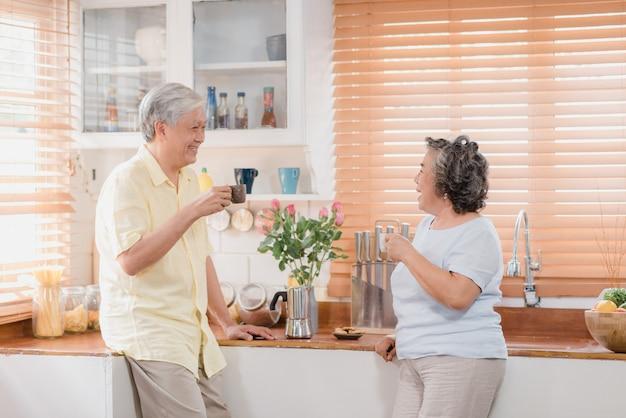 Pares idosos asiáticos que bebem o café morno e que falam junto na cozinha em casa.