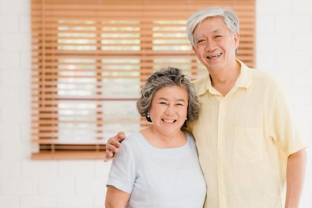 Pares idosos asiáticos que sentem o sorriso feliz e que olham à câmera quando relaxam na sala de visitas em casa.