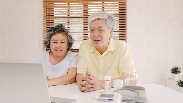 Pares idosos asiáticos que usam a conferência do portátil com o doutor sobre a informação da medicina na sala de visitas, par usando o tempo junto ao encontrar-se no sofá em casa.
