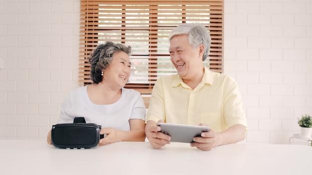 Pares idosos asiáticos usando o simulador da tabuleta e da realidade virtual que joga jogos na sala de visitas, par que sente feliz usando o tempo que encontra-se junto na tabela em casa.