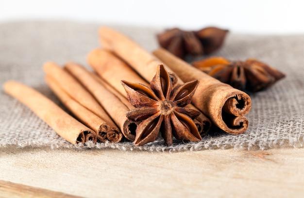 Pares inteiros de especiarias frescas e perfumadas de canela e estrelas de anis inteiras usadas na culinária, closeup