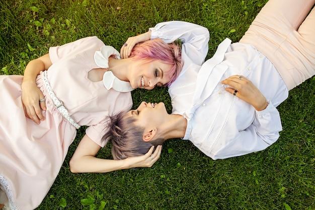 Pares lésbicas multirraciais que encontram-se na grama.