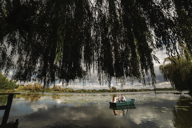 Pares loving que descansam em um lago ao montar um barco verde. romance.