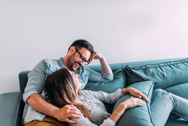 Pares loving que riem ao relaxar em casa.
