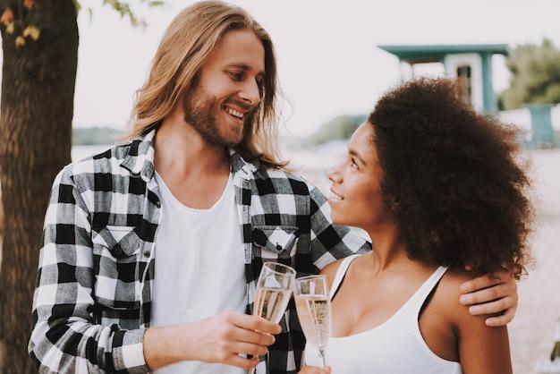 Pares multirraciais românticos champagne na praia.