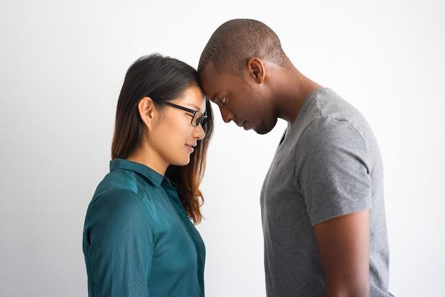 Pares multirraciais românticos que tocam em suas testas.
