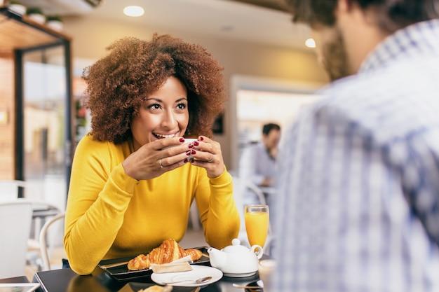 Pares na moda novos que bebem um café e um chá no café, comendo um croissant e sentindo feliz.