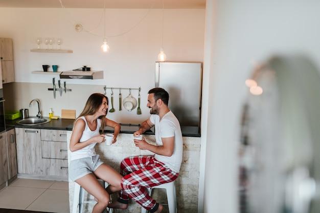 Pares nos pijamas que bebem o chá ou no café no contador de cozinha.