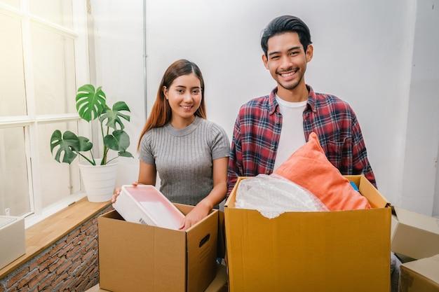 Pares novos asiáticos que levam a caixa de cartão grande para mover-se na casa nova