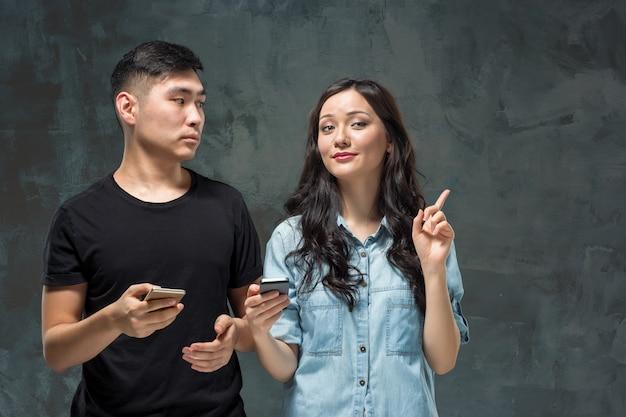 Pares novos asiáticos usando o telefone celular, retrato do close up.