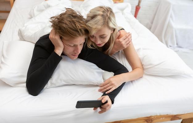 Pares novos com o smartphone que relaxa ao reclinar no noivo que senta-se na cama no quarto em casa.