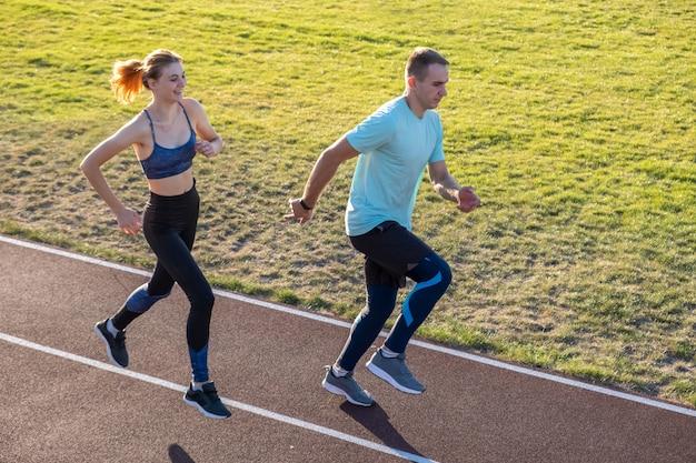 Pares novos de desportistas aptos menino e menina que correm ao fazer o exercício em trilhas vermelhas do estádio público ao ar livre.