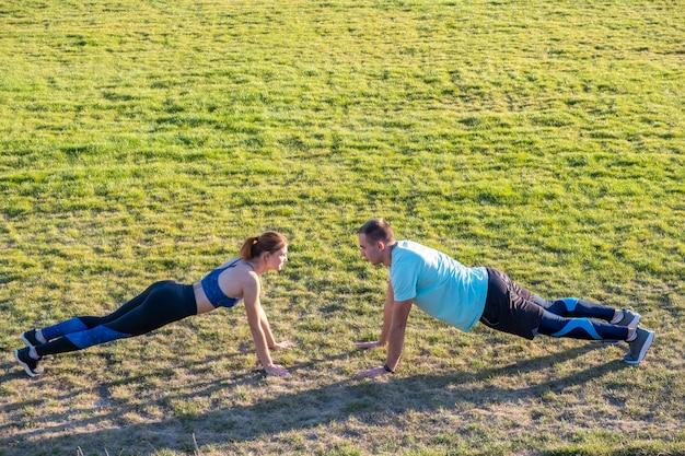 Pares novos de desportistas do ajuste menino e menina que fazem o exercício na grama verde do estádio público ao ar livre.