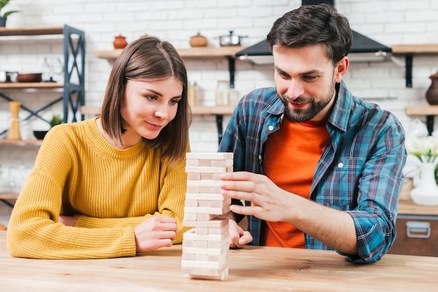 Pares novos de sorriso que jogam o jogo da torre dos blocos de madeira em casa