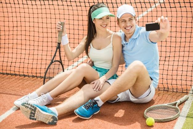 Pares novos de sorriso que sentam-se no campo de tênis.