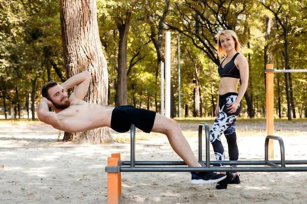 Pares novos desportivos que bombeiam os músculos abdominais em um parque no dia do outono.