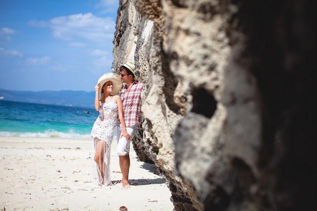Pares novos felizes bonitos na praia, contra o mar e as montanhas.