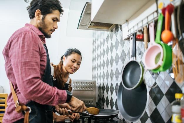 Pares novos felizes que ajudam-se que cozinha na cozinha em casa.