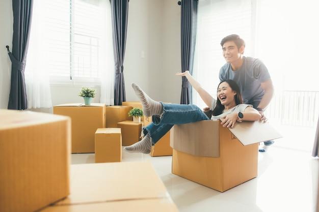 Pares novos felizes que apreciam junto mover-se em uma casa nova.