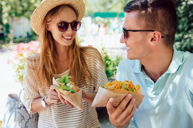 Pares novos felizes que comem o cachorro quente, passando o tempo com prazer, ao ar livre.