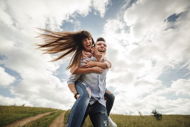 Pares novos loucos emocionalmente tendo o divertimento, beijando e abraçando ao ar livre.