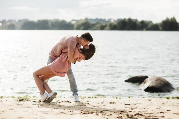 Pares novos loving que beijam e que abraçam dentro ao ar livre.