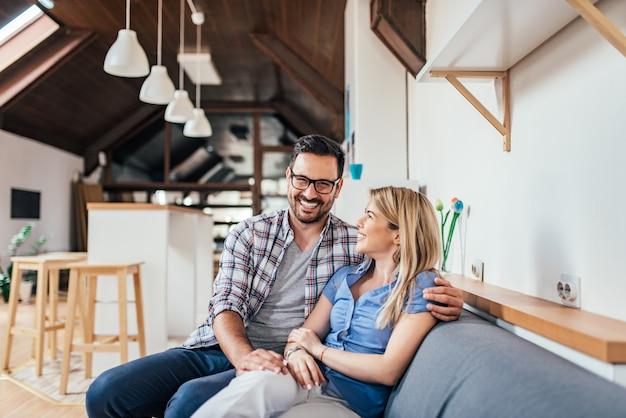 Pares novos loving que sentam-se no sofá no apartamento moderno.