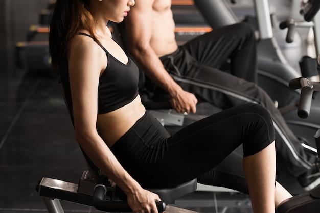 Pares novos nas bicicletas, grupo de jovens que exercitam em bicicletas no fitness center.
