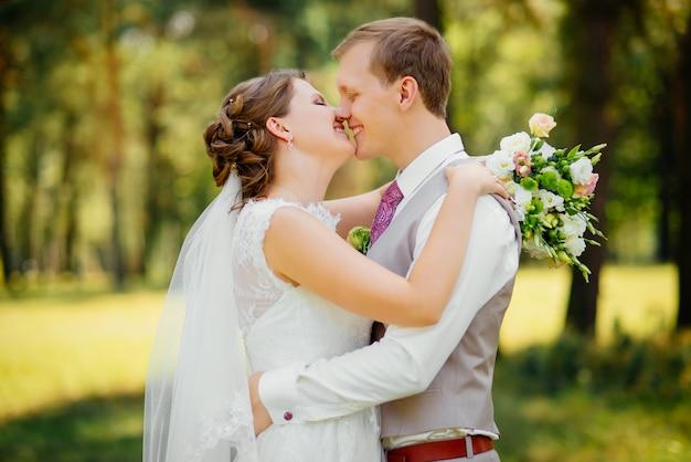 Pares novos no amor, no noivo e na noiva no vestido de casamento na natureza. casamento.