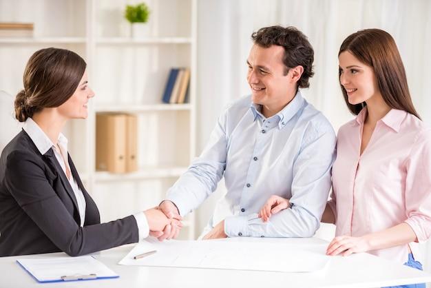 Pares novos que assinam o contrato financeiro com corretor de imóveis fêmea.