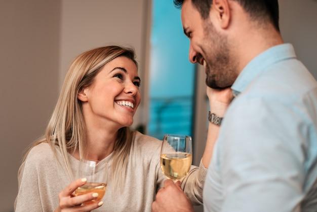 Pares novos que bebem o vinho branco e que riem em casa. fechar-se.