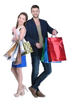 Pares novos que compram e que guardam muitos sacos de compras.
