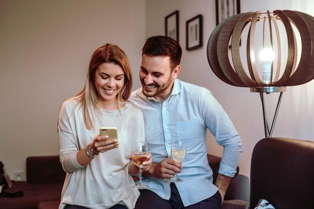 Pares novos que olham a tela de um telefone celular junto com sorrisos felizes.
