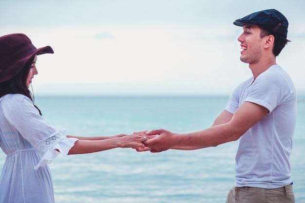 Pares novos românticos nos pares felizes da praia na praia branca em férias de verão.