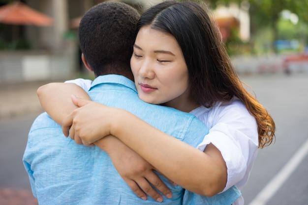 Pares ou amigos multi-étnicos novos tristes que abraçam fora.