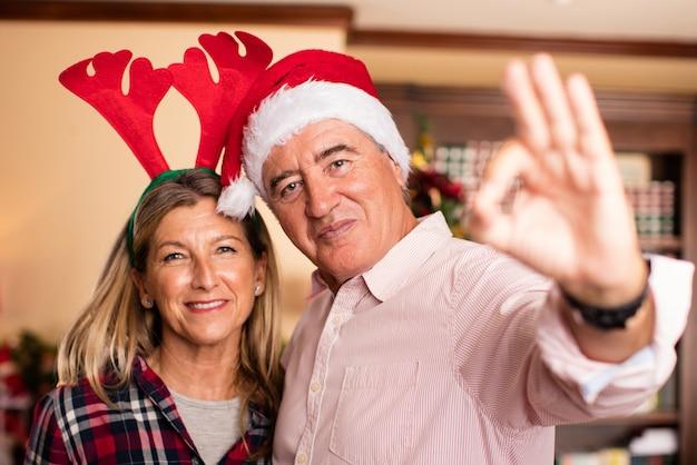Pares que abraçam com chapéu do natal dizendo okey