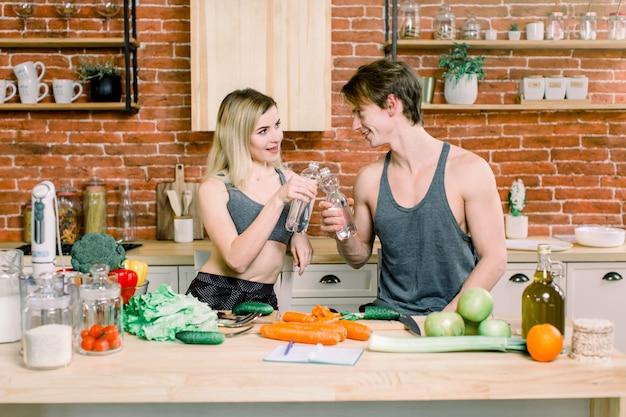 Pares que comem o alimento que alimenta o conceito doce. um casal feliz está preparando comida na cozinha e água potável