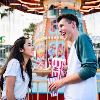 Pares que datam o conceito brincalhão festivo da felicidade do funfair do parque de diversões