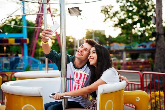 Pares que datam o conceito do divertimento do parque de diversões que abraça o conceito
