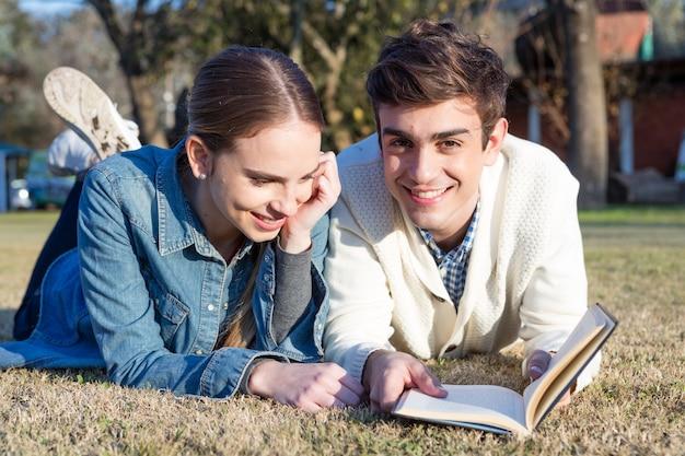 Pares que lêem um livro ao ar livre