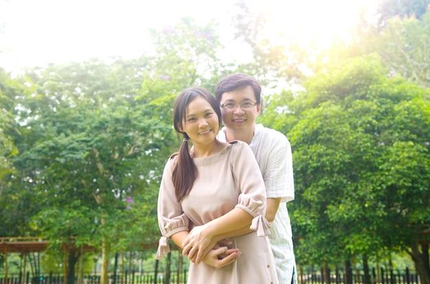 Pares romances asiáticos no amor no parque ao ar livre.