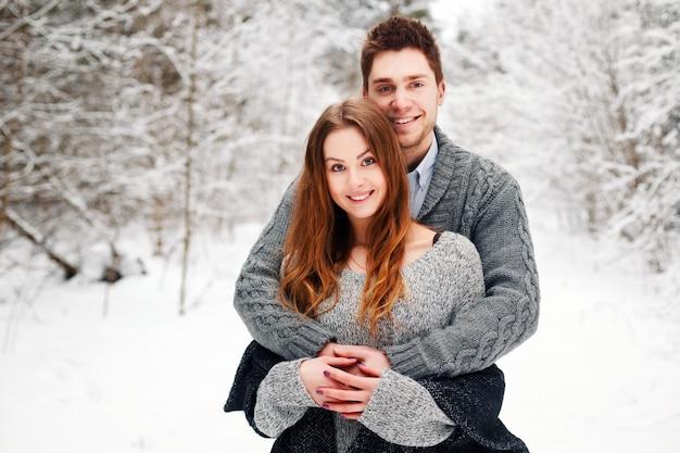 Pares românticos que abraçam na neve