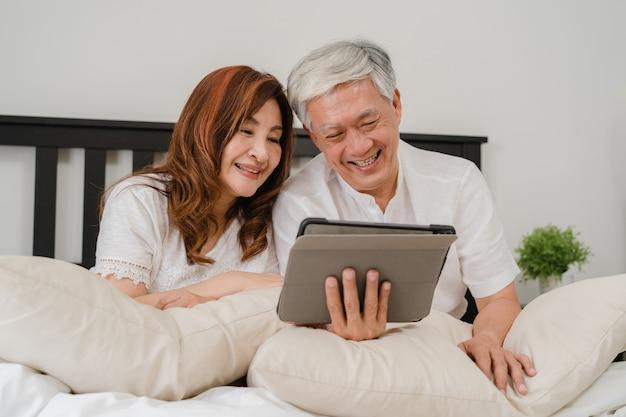Pares sênior asiáticos usando a tabuleta em casa. as avós chinesas sênior asiáticas, o marido e a esposa felizes após acordam, vendo o filme deitado na cama no quarto em casa no conceito da manhã.