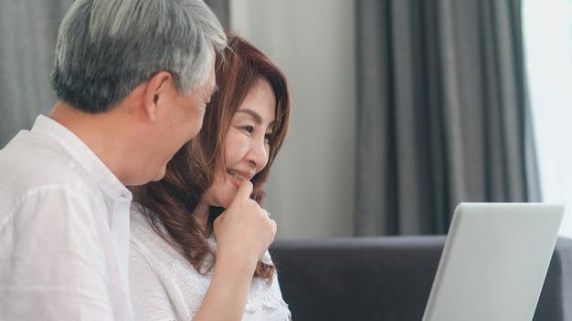 Pares sênior asiáticos usando o laptop em casa. as avós chinesas sênior asiáticas, surfam o internet para verificar meios sociais ao encontrar-se no sofá no conceito da sala de visitas em casa.