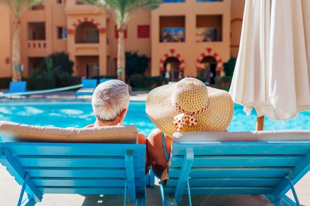 Pares sênior que relaxam pela piscina. pessoas curtindo férias. dia dos namorados