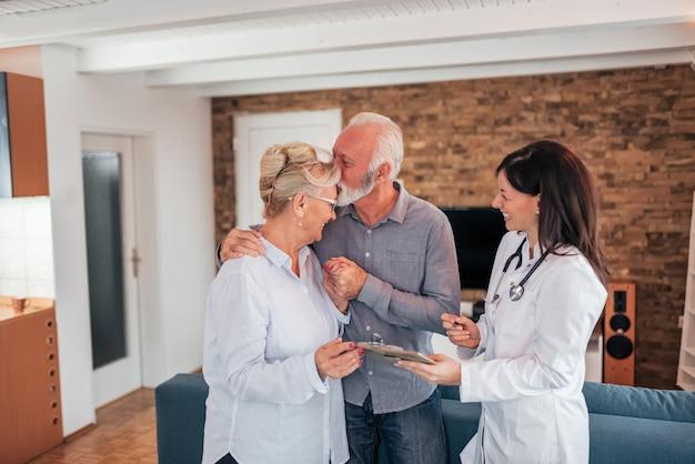 Pares superiores afetuosos que recebem boas notícias de um doutor em uma visita home.