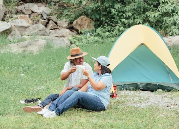 Pares superiores que apreciam a viagem de acampamento, bebem o café na manhã junto.