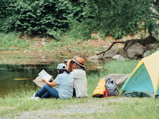 Pares superiores que apreciam acampando no parque natural.